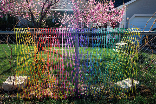 """Rainbow yarn stretched in triangular shapes on supports in a front yardGranary Arts """"Lawn Gnomes 2020"""" exhibit"""